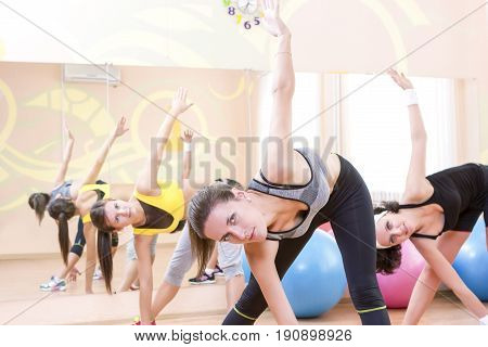 Fitnes and Stretching Conceots and Ideas. Three Happy Caucasian Female Athletes in Good Fit Having Stretching Exercises in Gym.Horizontal Image Composition