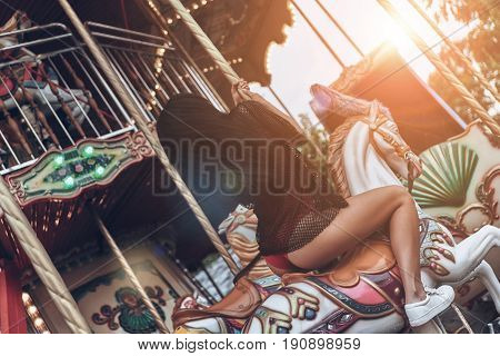 Merry-go-round fun. Rear view of beautiful young woman in red bikini riding merry-go-round