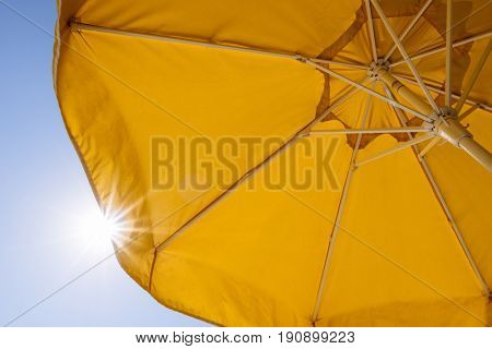Protection from the sun in a summer resort. Yellow umbrella on blue sky background