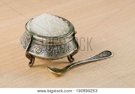Very old silver saltcellar with spoon on a wooden background.