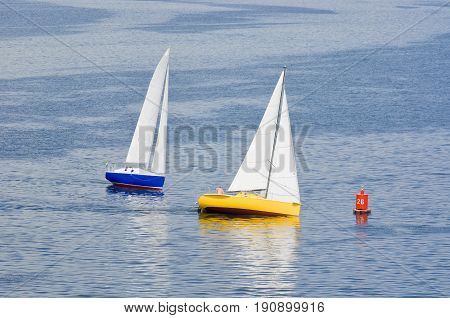 Two yacht making a turn near buoy on a summer river.