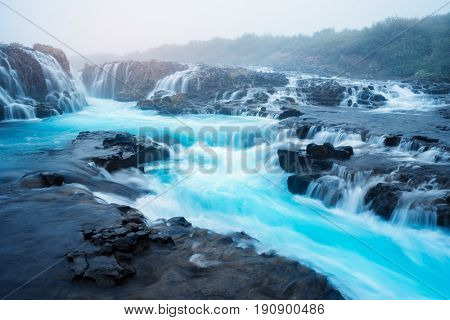 Landscape with an amazing waterfall Bruarfoss. Water is of turquoise color and beautiful cascades. Tourist attraction in Iceland. Morning fog