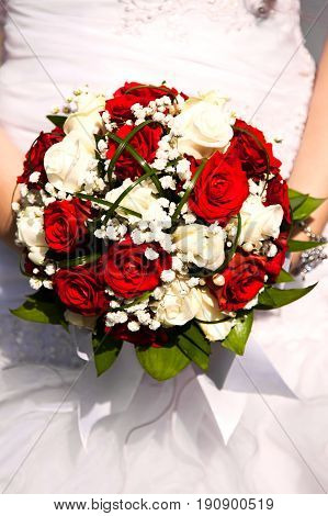 Bridal bouquet. The bride's . Beautiful of white flowers and greenery, decorated with silk ribbon, lies on vintage wooden chair, bouquet. Festive bouquet of the bride