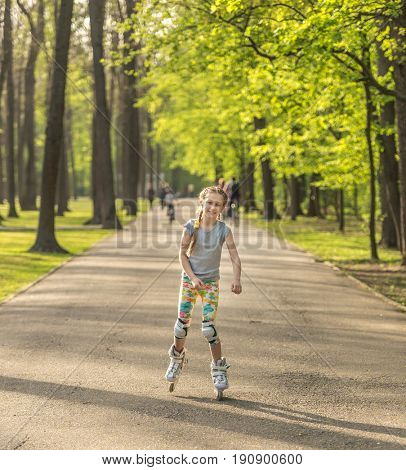 Teenage girl in the park, roller skating in colorful leggings, moving swiftly and professionaly