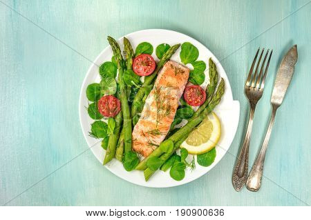 An overhead photo of a plate of grilled salmon with green asparagus, cherry tomatoes, corn salad, and a slice of lemon, a healthy diet dish with a place for text, a fork, and a knife