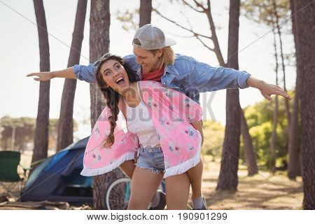 Young woman piggybacking man while standing at campsite