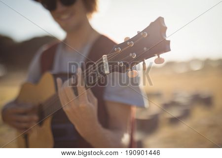 Close up of young man playing guitar while standing on field at forest