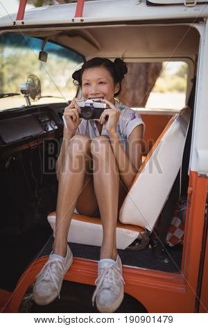 Cheerful woman holding camera while sitting in motor home at forest