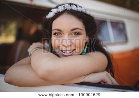 Portrait of smiling woman leaning on motor home