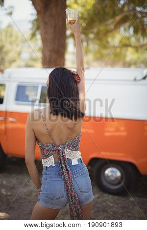 Rear view of sensuous young woman holding beer glass against van on field