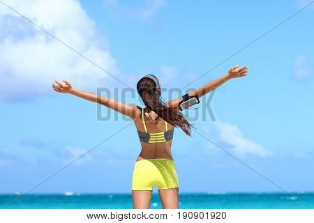 Fitness healthy lifestyle runner exercise success. Happy woman running with open arms in freedom listening to music with earphones and smartphone armband on blue copy space sky.