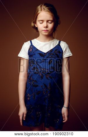 Portrait of a cute eight year old girl standing with serious face and closed eyes. Childhood concept.