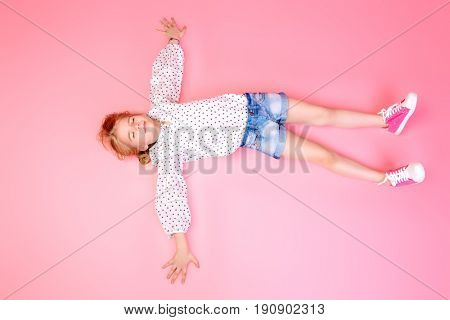 Happy childhood. Cute eight year old girl wearing summer jeans shorts and blouse lying over pink background. Studio shot.