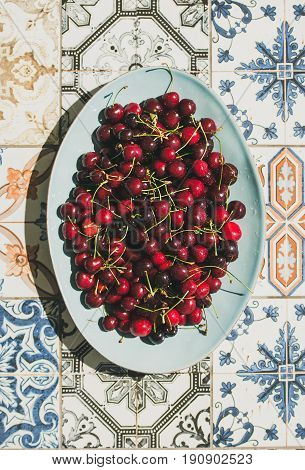 Fresh ripe sweet cherries in blue plate over colorful oriental ceramic tiles background, top view, flat lay. Summer food concept
