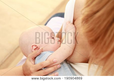indoor portrait of mother breast feeding and hugging her baby, at home