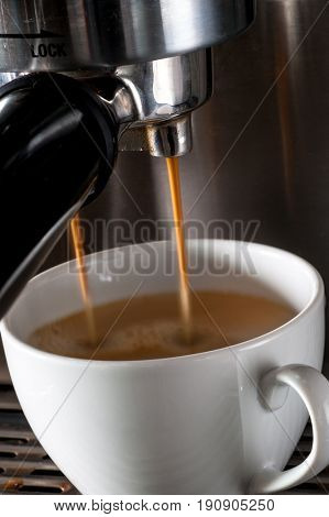 Espresso machine pouring strong looking fresh coffee into a cup