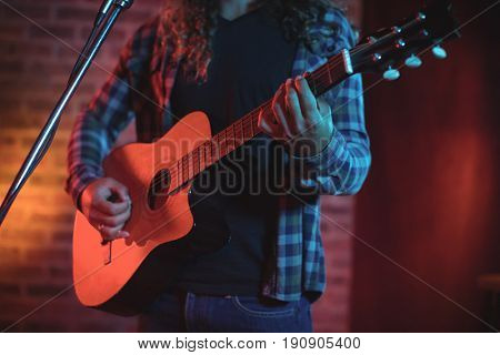 Mid section of singer playing guitar while singing in nightclub