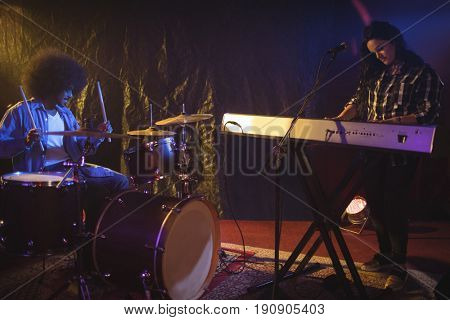 Female musician playing piano with male drummer in night club