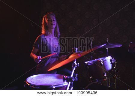 Confident female drummer performing in illuminated nightclub