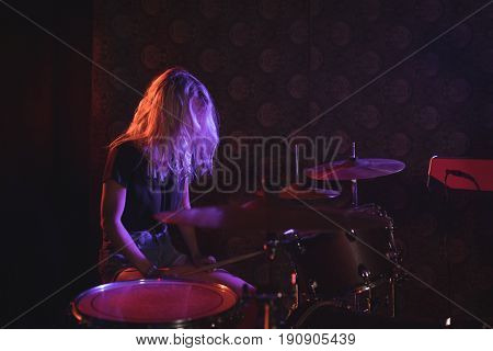 Female drummer performing on illuminated stage in nightclub
