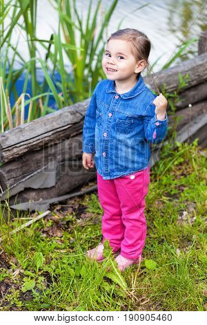 Small girl wearing in denim shirt posing near lake