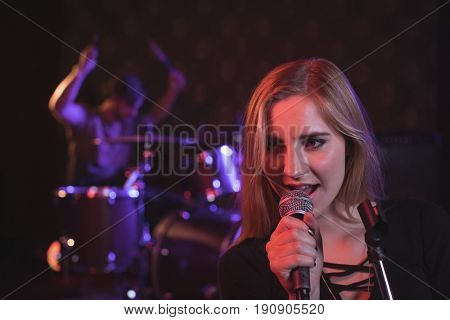 Close up of female singer performing with male drummer in nightclub