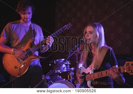 Male and female guitarists performing in nightclub