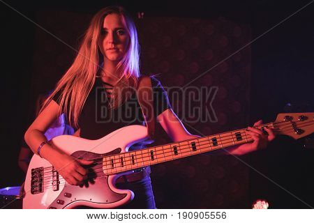 Portrait of young female guitarist performing in nightclub