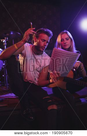 Low angle view of male and female musicians practicing with music sheets in nightclub