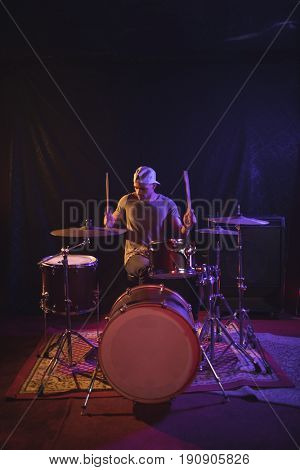 Confident male drummer performing in nightclub