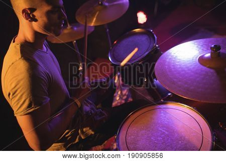 High angle view of drummer playing in illuminated nightclub