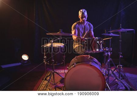 Serious male drummer performing in nightclub