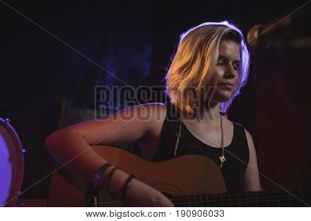 Close up of female playing guitar in nightclub