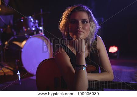 Portrait of confident female guitarist sitting in nightclub
