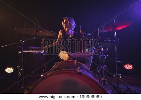 Confident female drummer playing drum kit in illuminated nightclub