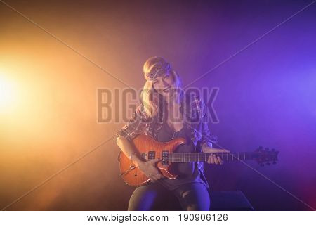 Portrait of confident female guitarist performing in music concert
