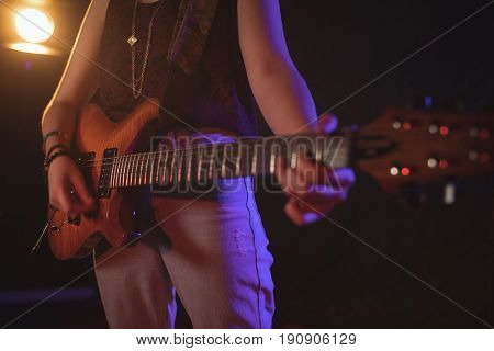 Mid section of female guitarist performing in music concert