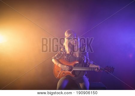 Confident female guitarist performing in illuminated nightclub