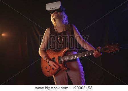 Female guitarist experiencing VR glasses while performing in nightclub