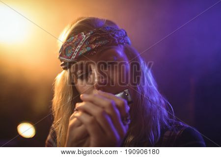 Close up of beautiful female musician playing harmonica in nightclub