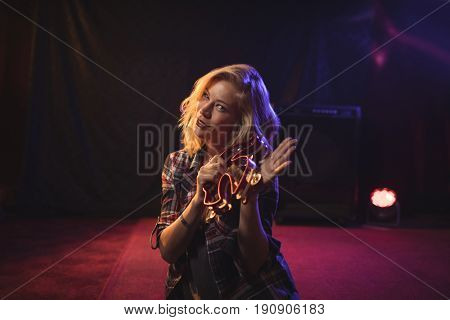 Portrait of beautiful female musician playing tambourine in nightclub