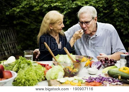 Senior adult couple eating salad outdoor