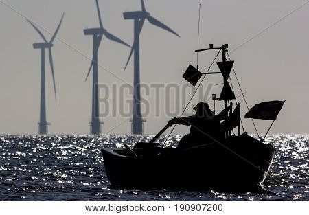 Green planet. Renewable energy offshore windfarm turbines and solitary fisherman. Tranquil scene of small fishing boat silhouetted at sunrise with sustainable energy wind turbines in the background.