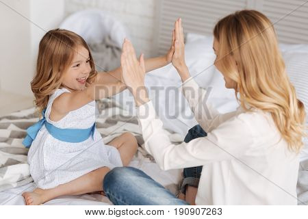 Playful mood. Cheerful smiling girl pressing her palms against the palms of her mother, playing with her a pat-a-cake game for children.