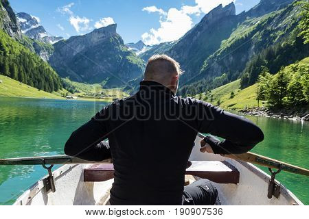 back of rower in front beautiful Seealpsee lake and Alpstein mountain in Appenzell Switzerland