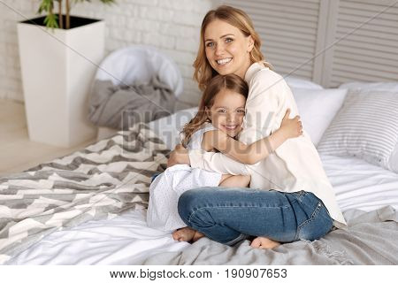 Sweet hugs. Charming little daughter and her lovely young mother sitting on the bed and hugging each other while looking at the camera and smiling