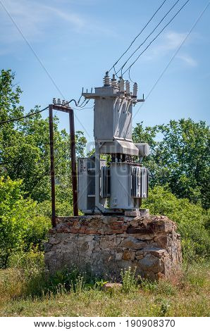 Electrical transformer on a stone stand. Old high-voltage power station.