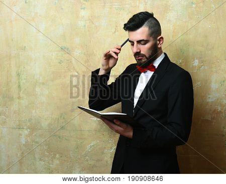 Young Businessman With Neat Beard And Haircut Reading Organizer