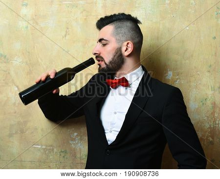 Young Classy Man With Tired Face Expression Drinks Alcoholic Beverage