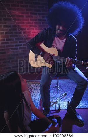 Female singer communicating with male guitarist while practicing in nightclub